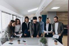 Volledige concentratie op het werk Groep jonge bedrijfs en mensen die terwijl status in modern bureau werken communiceren stock afbeelding