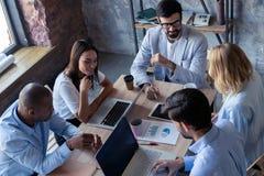 Volledige concentratie op het werk Groep jonge bedrijfs en mensen die terwijl het zitten bij het bureau werken communiceren stock afbeeldingen