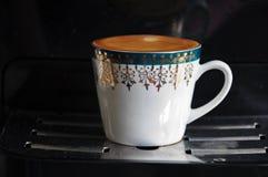 Volledige die kop van koffie, met kleurrijke ornamenten wordt verfraaid royalty-vrije stock afbeelding