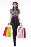Volledige die lengte van aantrekkelijke jonge de kleurendocument van de vrouwenholding het winkelen zakken op wit wordt geschoten Royalty-vrije Stock Foto