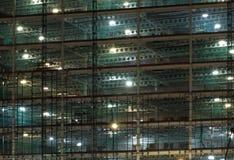 Volledige kadermening van een grote die bouwwerf bij nacht door heldere het werklichten wordt verlicht met balken en bouwhijstoes royalty-vrije stock afbeeldingen