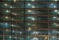Volledige kadermening van een grote die bouwwerf bij nacht door heldere het werklichten wordt verlicht met balken en bouwhijstoes stock foto
