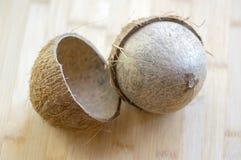 Volledige kokosnoot met notedoppen op houten bambolijst Stock Afbeeldingen