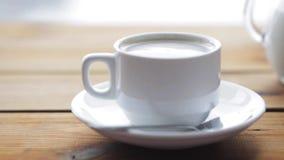 Volledige kop van koffie op houten lijst stock footage