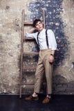 Volledige lengte modieuze mens in wit overhemd en beige broek met bretels die dichtbij oude houten ladder op bakstenen muurachter royalty-vrije stock fotografie