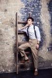 Volledige lengte modieuze mens in wit overhemd en beige broek met bretels het stellen en helling op oude houten ladder op baksten royalty-vrije stock afbeeldingen