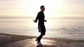 Volledige lengte van de lange, spier jonge mens die met touwtjespringen bij de kust uitoefenen Jonge mens belast met sport het we stock footage