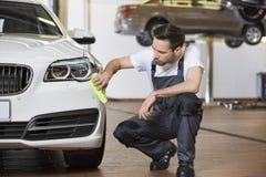 Volledige lengte van de schoonmakende auto van de onderhoudsingenieur in workshop Stock Afbeeldingen