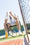 Volledige lengte van de uitgeputte rijpe mens met hoofd in handdoekzitting op stoel door netto bij tennisbaan op zonnige dag stock afbeelding