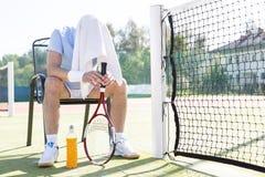 Volledige lengte van de vermoeide rijpe mens met behandelde hoofdzitting op stoel door netto bij tennisbaan op zonnige dag stock foto