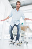 Volledige lengte van een gelukkige jonge mens die in bureau met een skateboard rijden Royalty-vrije Stock Afbeelding