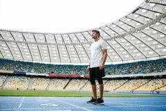 Volledige lengte van een jonge sportman die zich op een renbaan bevinden Stock Afbeeldingen