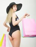 Volledige lengte van een mooie jonge dame in een badpak, grote zwarte hoed op hoge hielen, die kleurrijke zakken houden Het meisj Stock Foto's