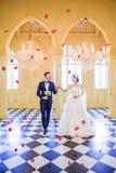 Volledige lengte van elegant huwelijkspaar die elkaar bekijken terwijl het lopen in kerk royalty-vrije stock fotografie