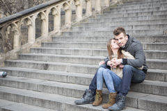 Volledige lengte van het houden van de vrouwen van kussende mens terwijl in openlucht het zitten op stappen Royalty-vrije Stock Afbeeldingen