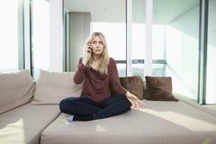 Volledige lengte van het jonge ontstemde vrouw spreken op mobiele telefoon thuis Stock Foto's