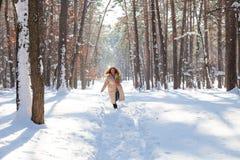 Volledige lengte van het opgetogen rode haired vrouw doornemen de winterbos met in hand narcissen royalty-vrije stock fotografie