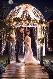 Volledige lengte van huwelijkspaar die in verlichte gazebo bij nacht dansen royalty-vrije stock afbeeldingen
