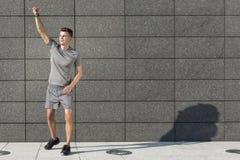 Volledige lengte van jonge jogger met dichtgeklemde vuist die zich tegen betegelde muur bevinden royalty-vrije stock foto