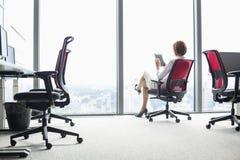 Volledige lengte van jonge onderneemster die tabletpc op stoel in bureau met behulp van stock afbeelding