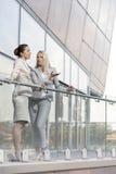 Volledige lengte van jonge onderneemsters die bij bureaubalkon converseren Stock Foto