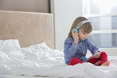 Volledige lengte van jongen het luisteren muziek op hoofdtelefoons in slaapkamer Stock Foto's