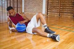 Volledige lengte van mannelijke basketbalspeler die mobiele telefoon met behulp van Stock Afbeelding