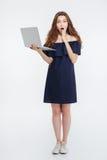 Volledige lengte van verbaasde jonge vrouw die en laptop bevinden zich houden Stock Foto