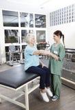Volledige Lengte van Verpleegster Putting Crepe Bandage op de Hand van de Patiënt Stock Afbeeldingen