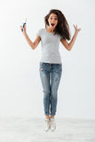 Volledige lengte van verraste leuke jonge vrouw met borstel het springen stock fotografie