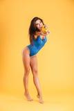 Volledige lengte van vrouw in het swimwear schieten met waterkanon Stock Foto's
