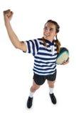 Volledige lengte van vrouwelijke het rugbybal van de atletenholding terwijl status met het dichtklemmen van vuist stock foto