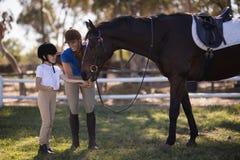 Volledige lengte van vrouwelijke jockey met zuster voedend paard royalty-vrije stock afbeeldingen