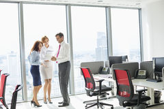 Volledige lengte van zakenlui die in bureau bespreken Stock Afbeeldingen