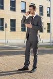 Volledige lengte van zakenman die celtelefoon met behulp van tegen de bureaubouw Royalty-vrije Stock Foto's