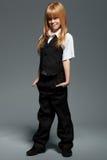 Volledige lengte weinig leuk meisje in wit overhemd, in zwart vest, in zwarte broeken, die over grijs worden geïsoleerd stock foto