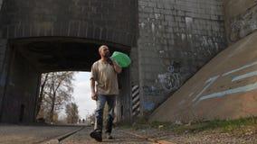 Volledige lengte werkloze mens die onder brug lopen stock videobeelden