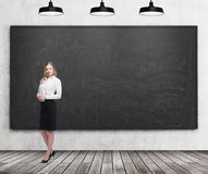 Volledige lengtedame in formele kleding Wit overhemd en zwarte rok Zwart bord op de muur, de houten vloer en Ce drie stock afbeelding