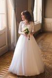 Volledige lengtemening van het mooie vrouw stellen in huwelijkskleding dichtbij venster bij luxebinnenland stock fotografie