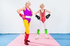 volledige lengtemening van sportieve hogere dames in bokshandschoenen die zich met handen bij taille en het glimlachen bevinden royalty-vrije stock foto's