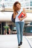 Volledige lichaams gelukkige vrouwelijke student die buiten met cellphone lopen royalty-vrije stock foto's