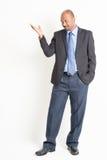 Volledige lichaams rijpe Indische zakenman die iets tonen Stock Foto's