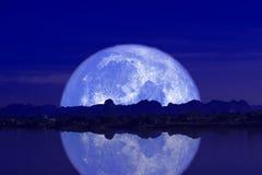 volledige melkmaan terug bij de silhouetberg en bezinning over de hemel van de riviernacht royalty-vrije stock fotografie