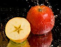 Voller Apfel und Hälfte mit dem Wasserspritzen Lizenzfreie Stockbilder