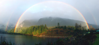 Voller doppelter Regenbogen über See Lizenzfreie Stockfotografie