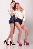 Voller Körper von zwei sexy hohen Modellen auf grauem Hintergrund Stockbild