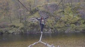 Voller Körperschuß einer jungen Frau, die eine Drahtbrücke über dem Nevis-Fluss, Schottland kreuzt stock footage