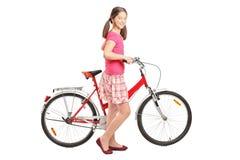 In voller Länge Portrait ein Mädchen, das ein Fahrrad anhält Lizenzfreies Stockfoto