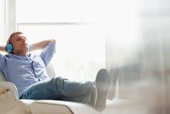 In voller Länge vom entspannten Mann von mittlerem Alter, der zu Hause Musik hört Lizenzfreie Stockbilder