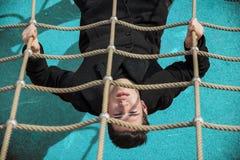 In voller Länge vom ernsten Mann 20s auf climbling Seil Lizenzfreie Stockfotos